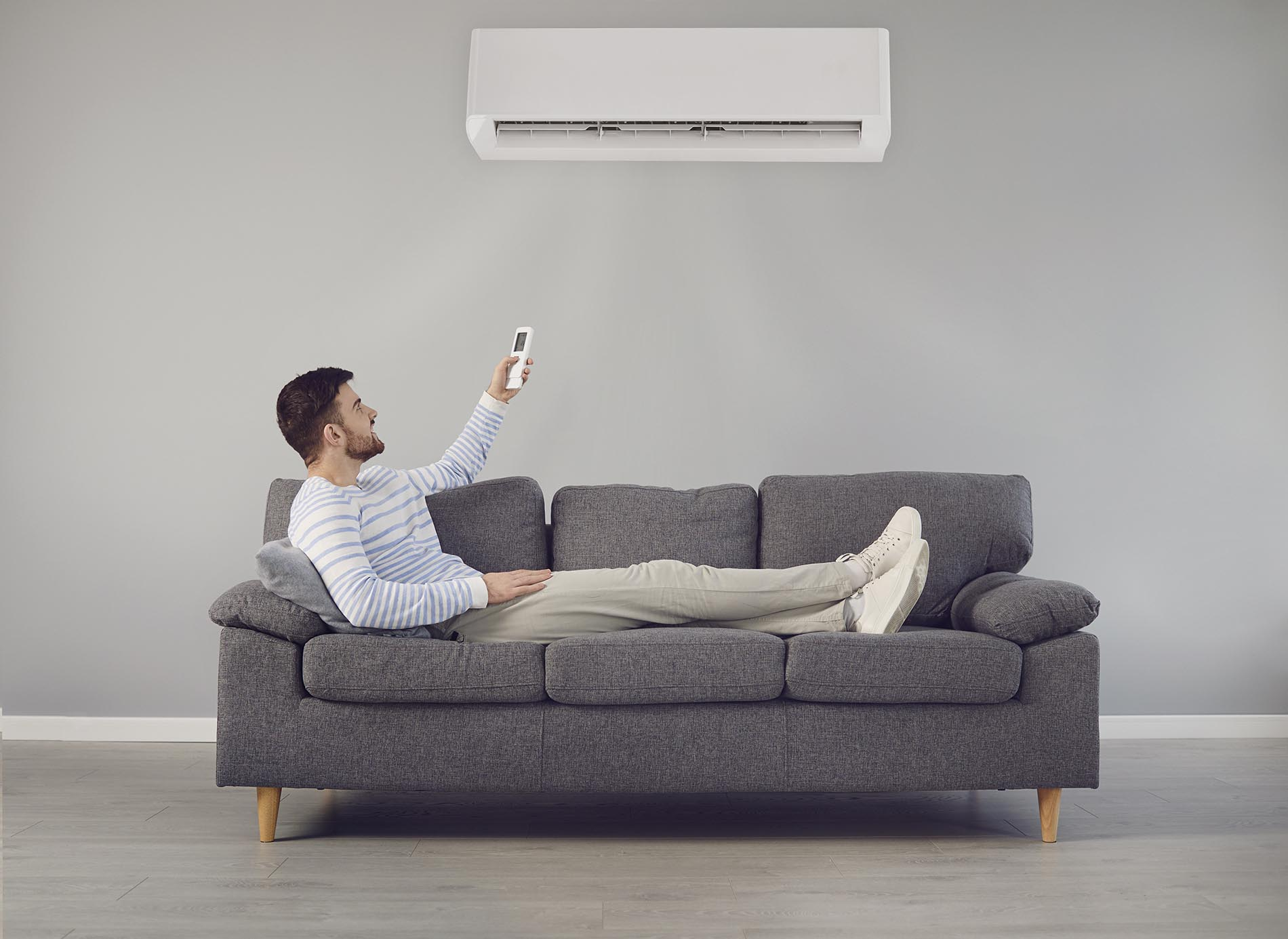 The young man turns on the air conditioner cools the air while sitting on the sofa in the room.